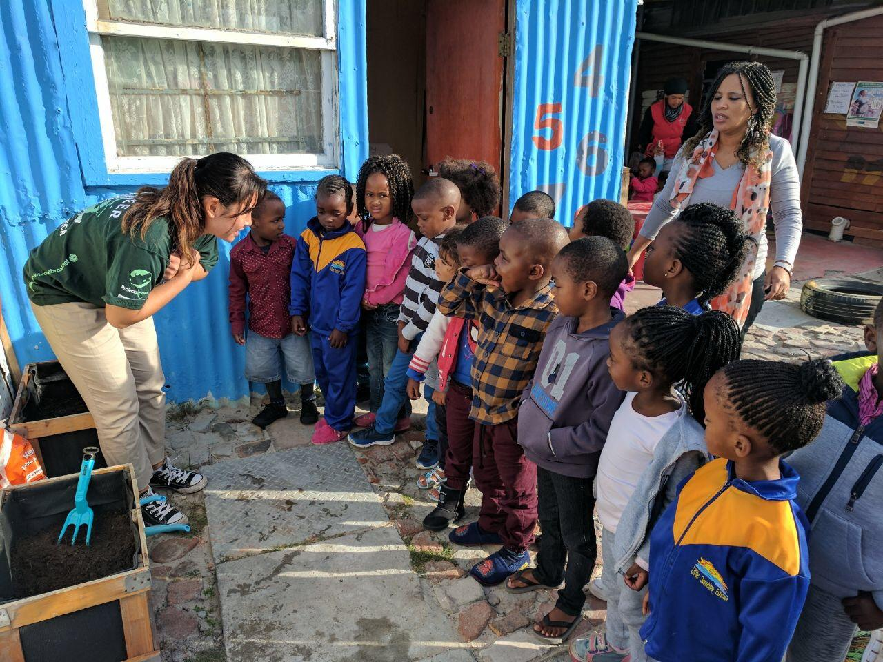 A female intern from Projects Abroad is pictured teaching a group of children about growing vegetables as part of her nutrition internship in South Africa.